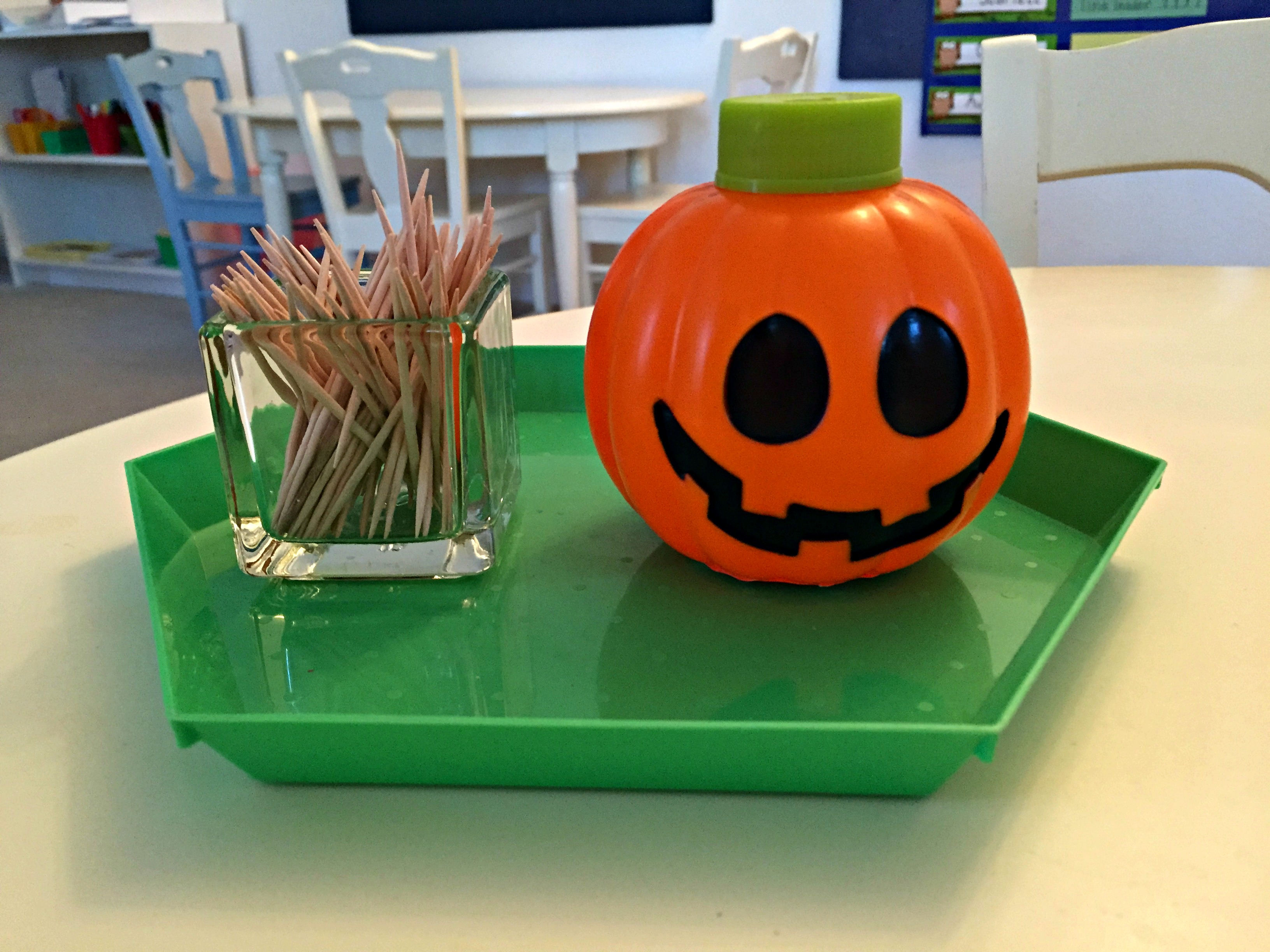 halloween practical life activity dropping toothpicks in a pumpkin container
